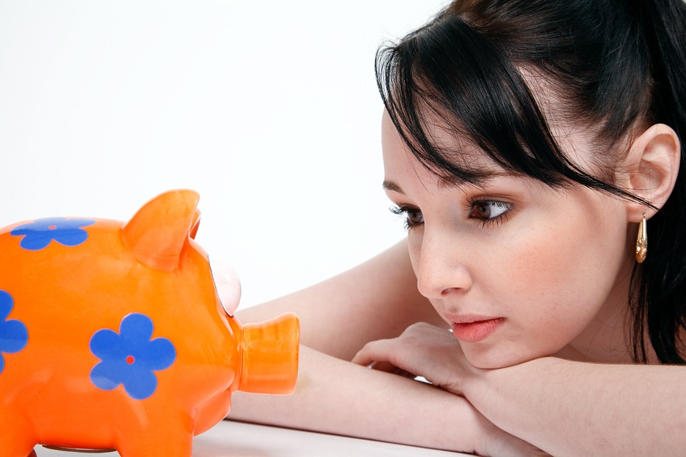 Renting vs. Owning - Can you afford three percent down? Young woman looking at a piggy bank